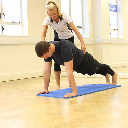 Physiotherapist assisting client with a press up