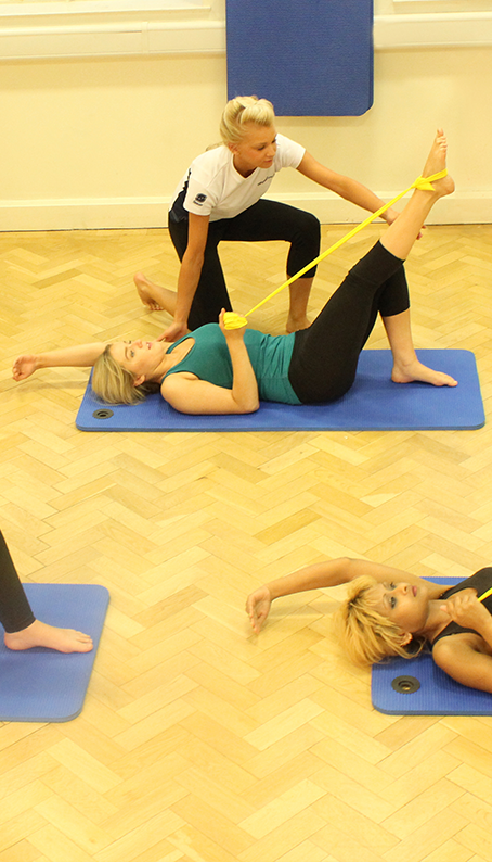 Instructor assisting client with pilate stretches