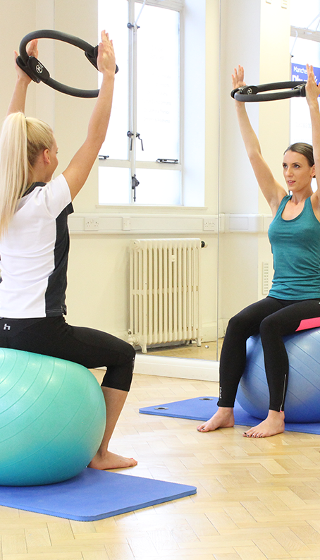 Client and Instructor sitting on pilates ball with a Pilates ring