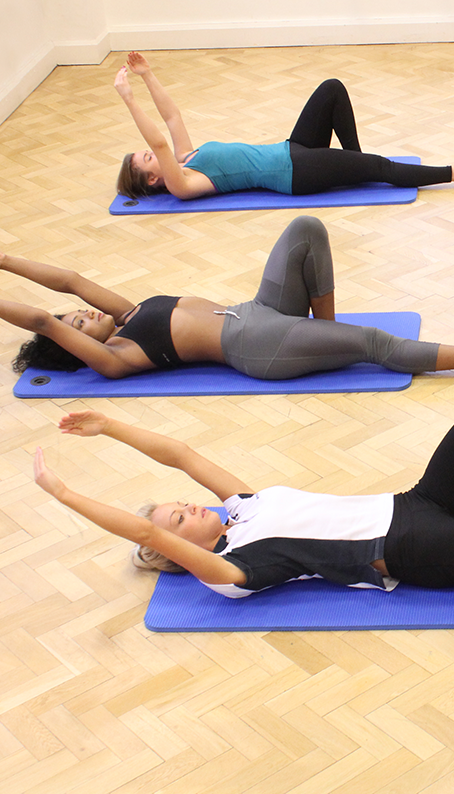 instructor with clients stretching on a Pilates mat