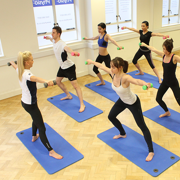 Medium size Pilates class using dumbells during an excercise