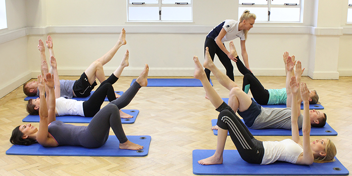 Pilates class completing leg and arm stretches