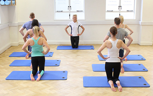 Pilates instructor assisting a group with exercises