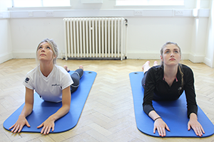 Client and instructor doing pilates on a Pilates mat