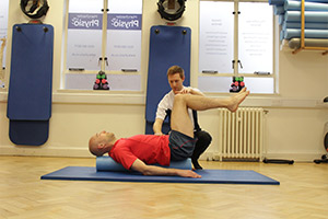 Client being assisted on a Pilates mat