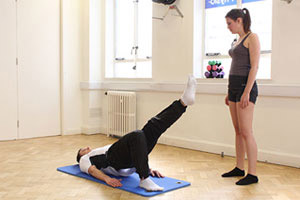 Pilates instructor showing client how to do pilates.