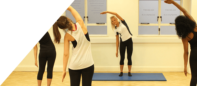 Pilates class completing over the head arm stretches