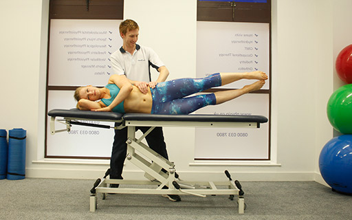 Pilates instructor assisting a client on an exercise bed