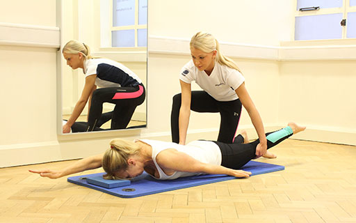physiotherapist guiding a client on a Pilates mat