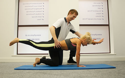 Pilates instructor helping a client with pilates exercises.