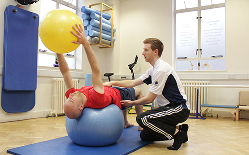 Pilates instructor helping a client on a physioball