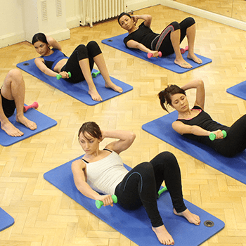 Pilates class using dumbbells and mats during excercise