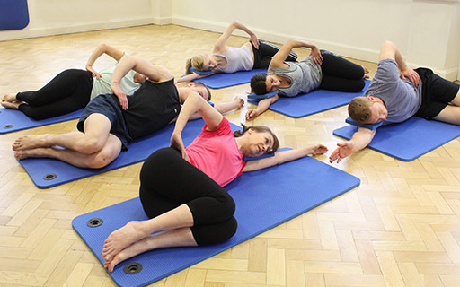 Group class stretching whilst lying on a Pilates mat