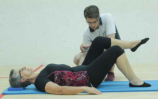 Pilates instructor helping client get maximum results in a Pilates exercise.