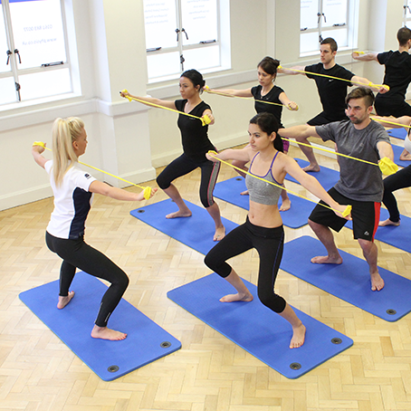 Pilates Instructer showing a class the correct usage of resistant bands