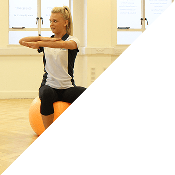 Instructor stretching arms whilst on gym ball