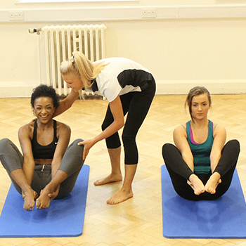 Instructor having fun with class member during stretch