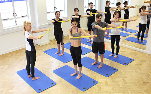 Physiolates instructor demonstrating pilates exercises for a group session