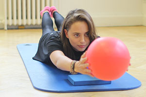 client using pilates ball on mat